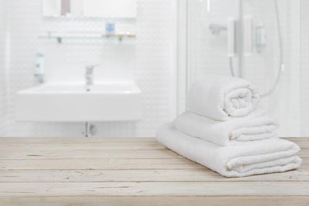 Niewyraźne tło wnętrza łazienki i białe ręczniki spa na drewnie
