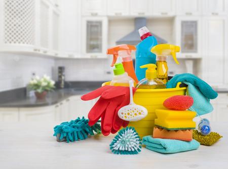 Kom met schoonmaakproducten op tafel over vervaagde keukenachtergrond Stockfoto