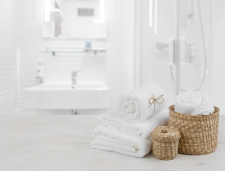 White spa towels and wicker baskets on defocused bathroom interior