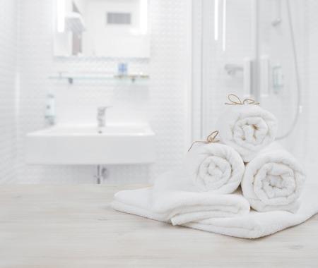 White folded spa towels on defocused interior background of bathroom