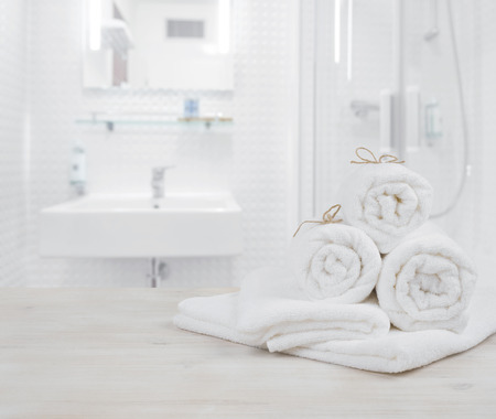 White folded spa towels on defocused interior background of bathroom