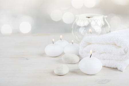 Spa resort therapy composition. Burning candles, stones, towel, abstract lights Reklamní fotografie - 65741411