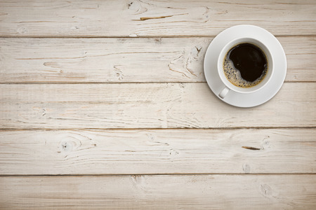 coffee table: Coffee cup with saucer on wooden planks background, top view Stock Photo