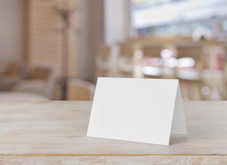 Tischkarte des leeren Papiers auf Holztisch über Barhintergrund