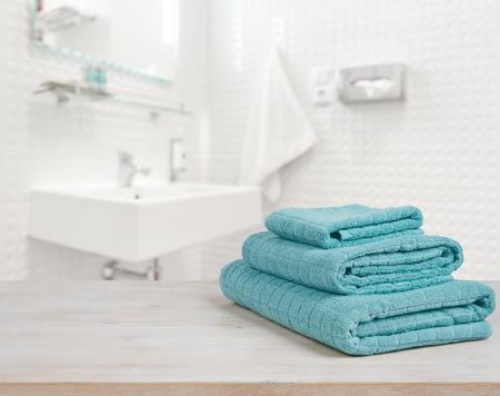 Turquoise spa handdoeken stapelen op hout over onscherpe achtergrond badkamer