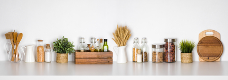 Kitchen shelf with various herbs, spices, utensils on white background