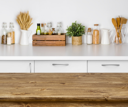 Brown wooden table with bokeh image of kitchen bench interior Archivio Fotografico