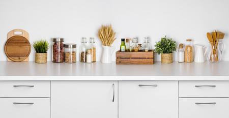 様々 なハーブ、スパイス、白の上の器具で台所のベンチ棚