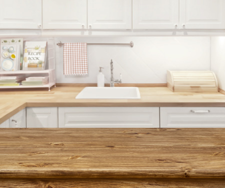 Blurred kitchen interior with wooden dinning table in front Archivio Fotografico