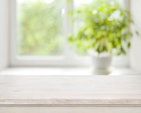 Lichte houten tafel op defocuced lente venster achtergrond Stockfoto