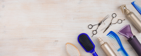 Professional hairdresser tools on wooden surface with copyspace at left