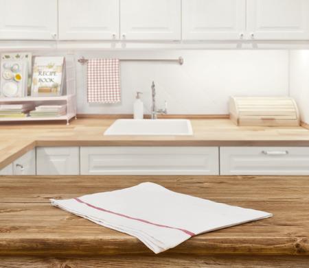 полотенце: Деревянный стол обеденного с салфеткой перед размытыми кухнями