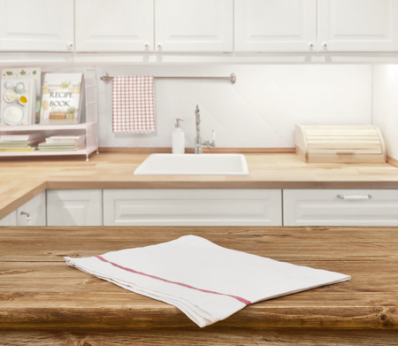Wooden dinning table with napkin in front of blurred kitchen Foto de archivo