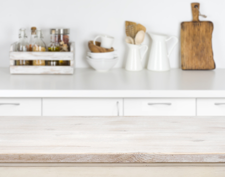 Light wood table with bokeh image of kitchen counter interior Archivio Fotografico