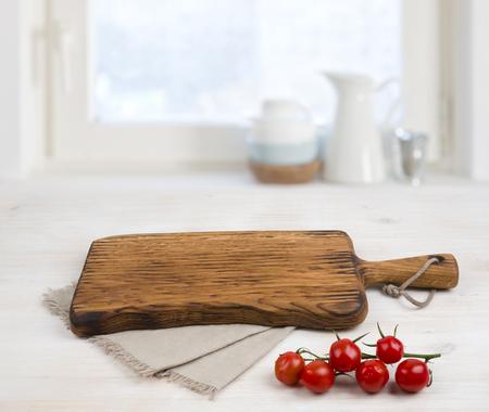 Deska do krojenia powyżej lnianym obrusem na drewnianym stole. pojęcie gotowanie