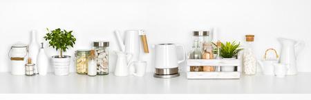 Kitchen shelf full of various utensils isolated on white background