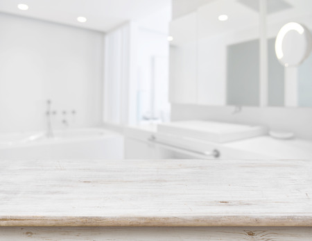 Background of blurred bathroom interior with wooden table in front Reklamní fotografie - 78363431