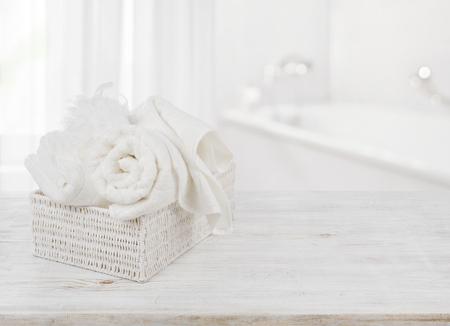 Handdoeken en bad spons in doos over wazige badkamer achtergrond Stockfoto