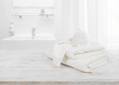 Fluffy towels and wisp of bast over blurred bathroom background Archivio Fotografico