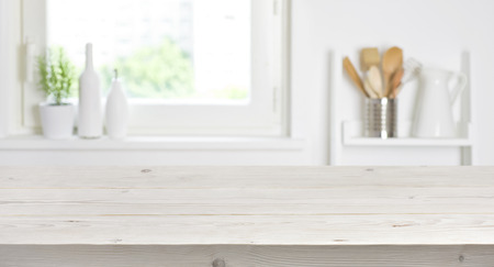 Wooden table on blurred background of kitchen window and shelves Standard-Bild