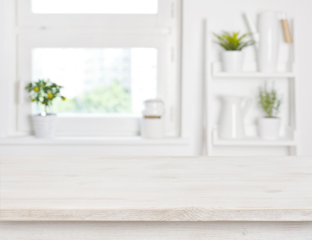 Empty bleached wooden table and kitchen window shelves blurred background Foto de archivo