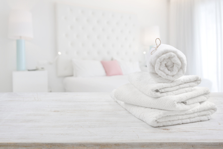 White towels on wooden surface over blurred bedroom interior background Foto de archivo