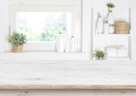 Wooden table on blurred background of bathroom window and shelves
