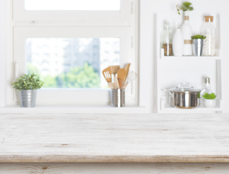 Empty table on blurred background of kitchen window and shelves