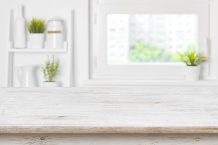 Empty textured wooden table and kitchen window shelves blurred background Foto de archivo