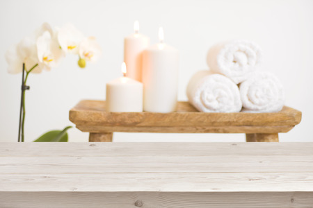Wooden table in front of blurred background of spa products