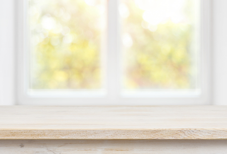 Wooden table top on blurred glass window wall building background