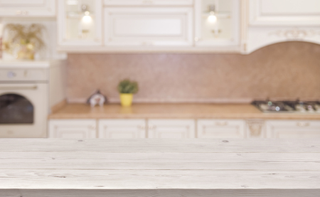 Blurred kitchen interior background with wooden planks table in front Stok Fotoğraf