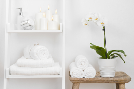 Shelf with clean towels, candles, flowerpot on bathroom wooden table Foto de archivo