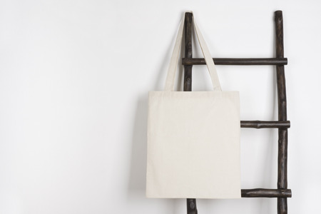 Fabric cloth shopping bag mockup hanging on vintage wooden stepladder 写真素材 - 93211478