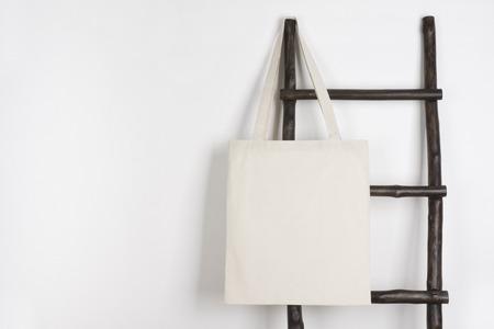 Fabric cloth shopping bag mockup hanging on vintage wooden stepladder