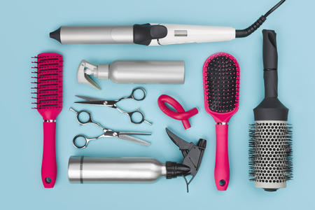 Professional hairdressing tools isolated on blue background, view from above