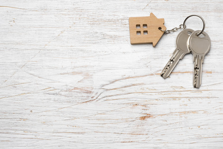 House symbol with silver keys on wood. Real estate concept