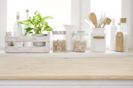 Wooden table over blurred kitchen window sill for product display