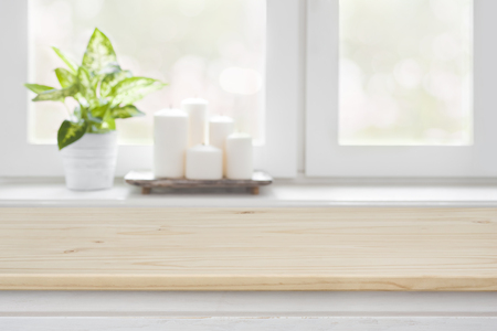 Wooden table over blurred window sill background for product display Foto de archivo