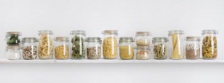 Assortment of uncooked groceries in glass jars arranged on shelf Stok Fotoğraf