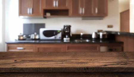 Wooden table in front of defocused modern kitchen counter top