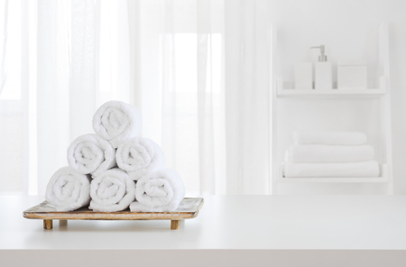 White towels on wooden pedestal over blurred spa room