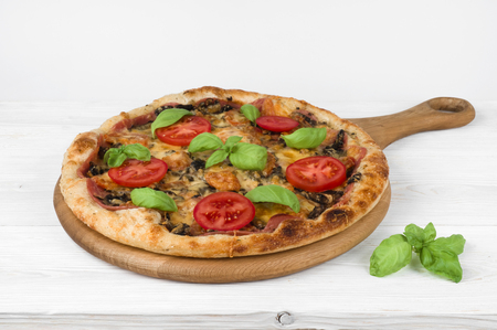 Tasty fast food traditional Pizza on wooden kitchen table