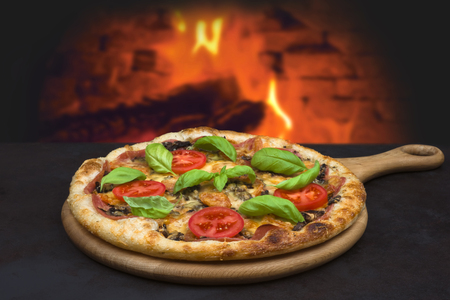 Traditional baked pizza on  blurred brick oven fire