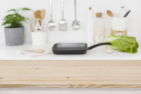 Defocused kitchen cooking place with empty wooden table in front