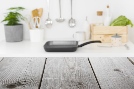 Rough wooden planks in front of defocused kitchen cooking place Banco de Imagens