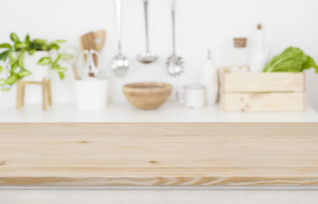 Wooden table top over blurred kitchen utensils for product display Banco de Imagens