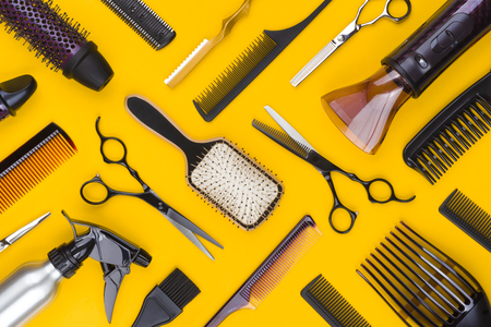 Top view of hairdresser tools and accessories on yellow Banco de Imagens