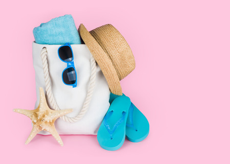 Beach vacation concept with flip-flops and bag on pink