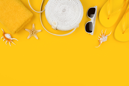 White handbag with beach accessories on yellow Banco de Imagens
